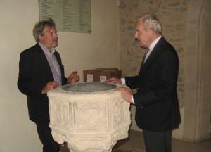 Simon Keyes, Director of the St Ethelburga's Centre shows Michael Henderson the font where Henderson was baptised (Photo: Michael Smith)